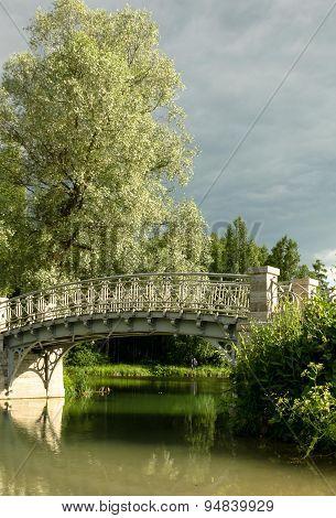 Beautiful delicate bridge across the river in the park