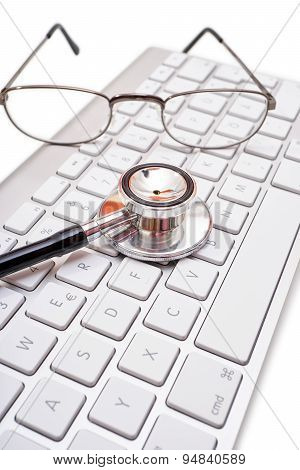 Stethoscope And Glasses On Computer Keyboard