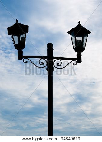 Silhouette of a street lamp against the blue cloudy sky