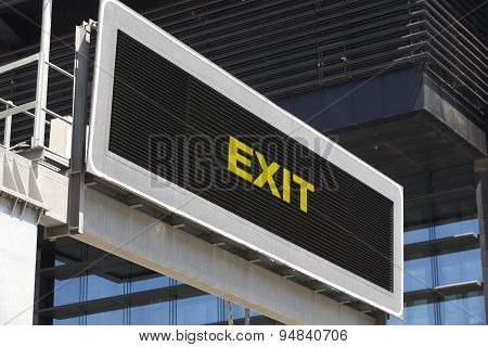 Exit Traffic Signpost In The City With Building Facade Background