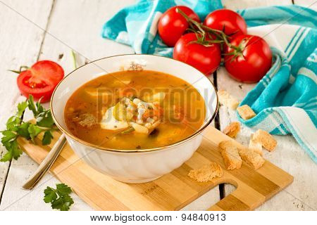 Solyanka, meat and pickle soup on in a white ceramic bowl on a white wooden background.