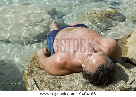 man sunbathing on rocks