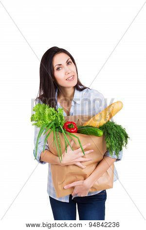 Happy young woman holding paper bag with groceries. Smiling girl customer. Consumerism. Isolated on