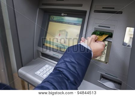 People Stand In A Queue To Use The Atms Of A Bank. Person Receiving Money From The Atm.