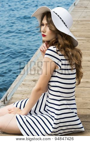 Girl Sitting On Bridge Sea In Summer Day