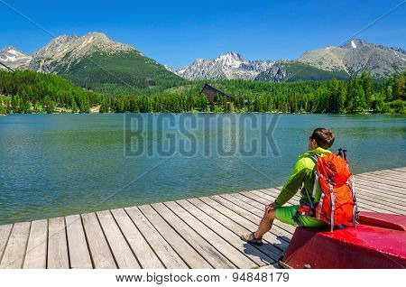 Young man with orange backpack on red boat