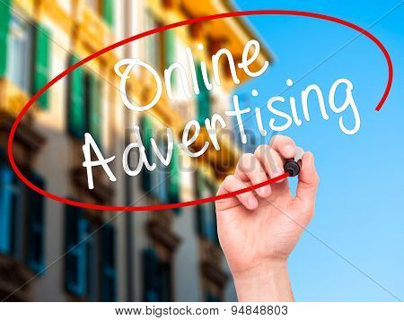 Man Hand writing Online Advertising with black marker on visual screen.