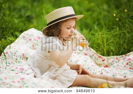 Little Girl In A Hat Drinking A Juice
