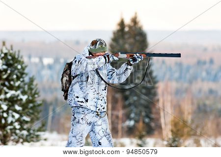 The Hunter In Winter Camouflage Shooting From A Gun