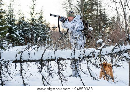 Hunter Takes Aim From A Gun In The Winter Forest