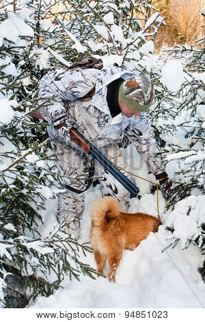 Hunter With Dog Is Looking For A Trail In The Snow