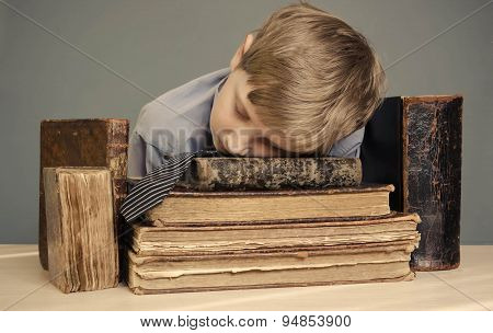 boy teenager sleeping on old books