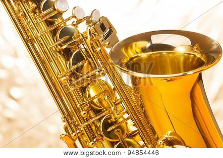Saxophone with bell and keys on silver background