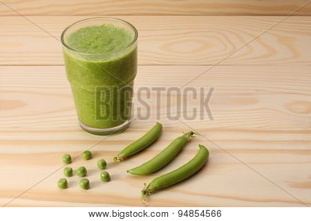 Smoothie With Green Peas  In A Glass And Pea Pods  On Wooden Table