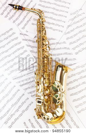 Shiny alto saxophone in full size on musical notes