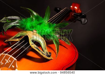Venetian mask with green feathers on violoncello