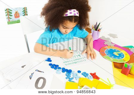 Concentrated African girl writes letters at table