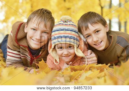 Children lying on yellow leaves