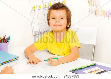 Boy draws with pen during sitting at table