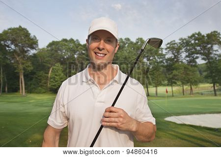 Handsome Young Smiling Golfer Holds Club On A Course