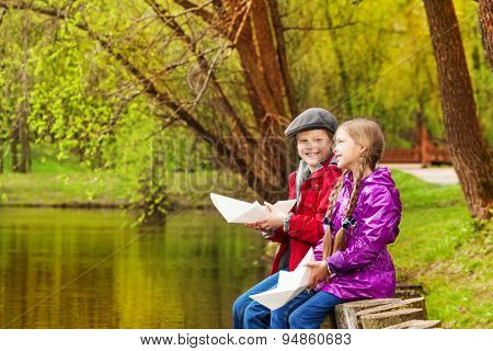 Smiling girl and boy sit near nice pond playing