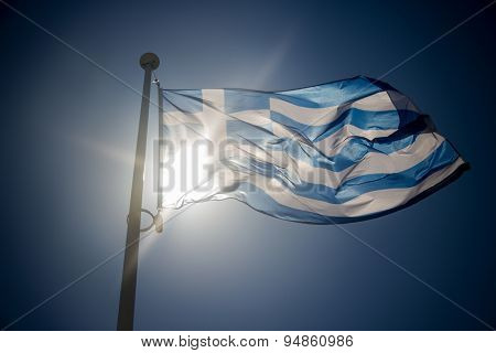 Greek Flag Waving Before Sun On Blue Sky