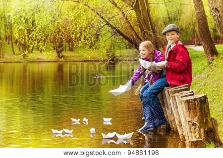 Cute girl and boy play with paper boats on pond