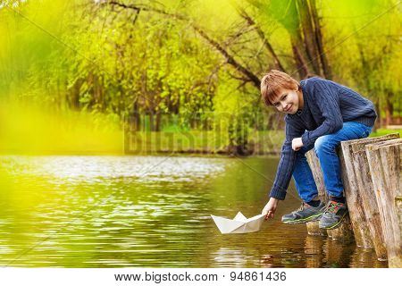 Smiling boy plays with white paper boat near pond