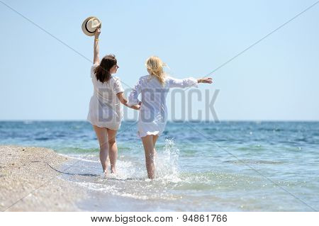 Two Womans In White Dress Running On The Beach