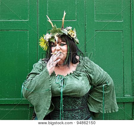 Woman in green costume smoking