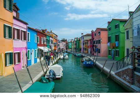 BURANO, ITALY - APRIL 2014: Colourful houses along a canal on Burano island, Italy