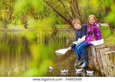 Boy hug girl near the pond putting paper boats