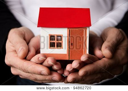 Pair of hands holding a paper house as symbol of home care. House insurance