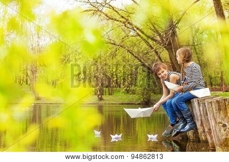Boy and girl play with paper boats on river water