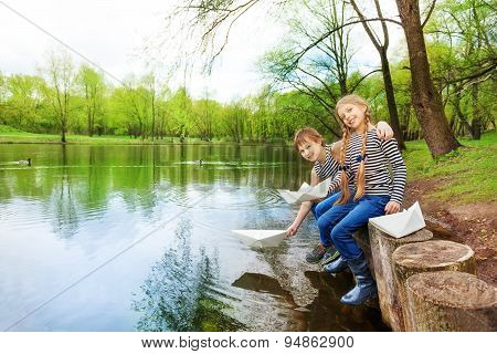 Boy, girl in striped shirts play with paper boats