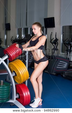 Girl with perfect body performing barbell exercise in gym