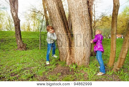 Boy with girl play hide and seek in the forest