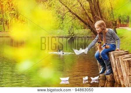 Girl sitting near pond playing with paper boats
