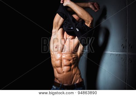 Muscular and sexy torso of young man taking off his shirt