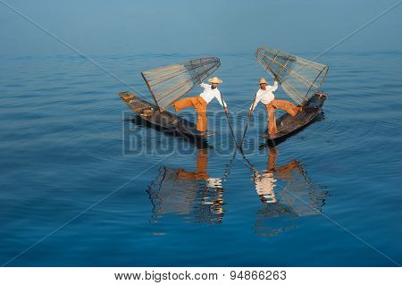 Burmese fisherman on bamboo boat catching fish in traditional way. Inle lake, Myanmar