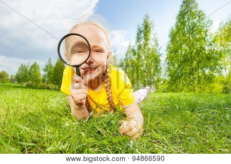 Positive girl with magnifier lays alone on  grass