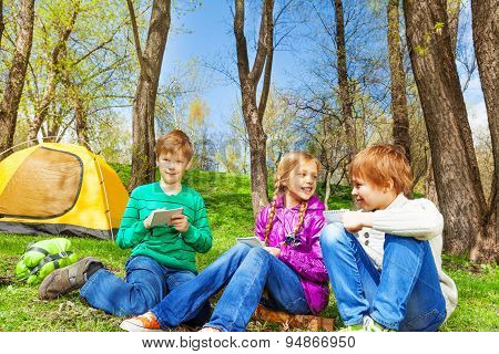 Happy kids resting together sit near yellow tent