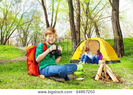 Happy boy with red backpack and binocular at camp