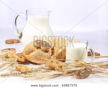 Milk In A Transparent Jug And A Roll From Wheat Flour Of A House Batch On A White Background