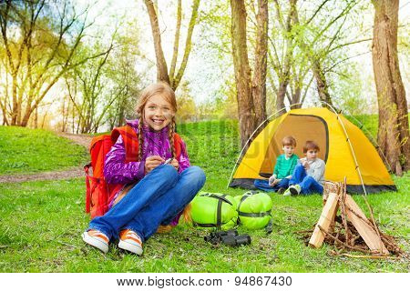 Happy children relax near the wooden bonfire, tent