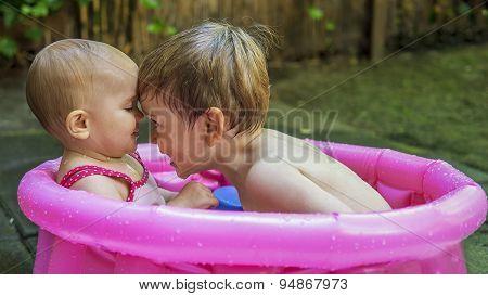 Siblings Playing In A Tub