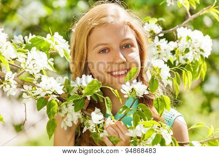 Smiling teenager girl with flowers on pear tree