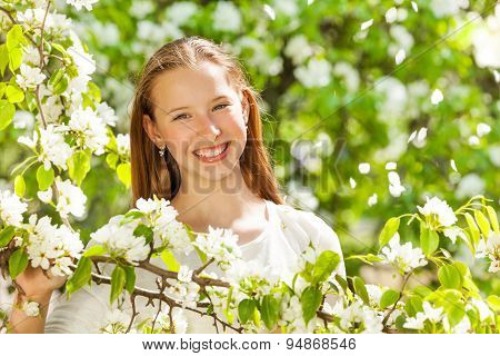 Happy teenager girl with white flowers on tree