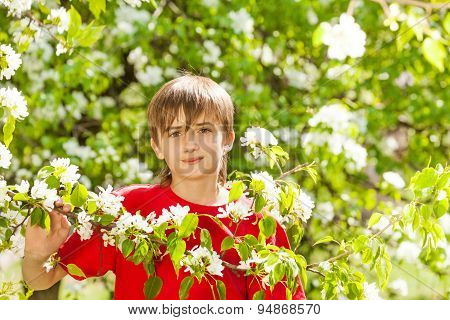 Teenager boy holds branch with white flowers