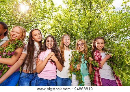 Smiling teenage girls standing and holding benches